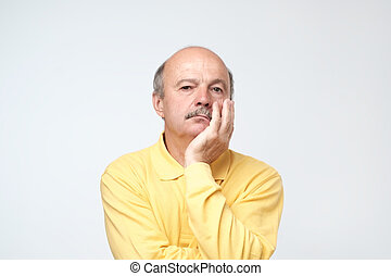 Closeup portrait of sleepy mature man in yellow t-shirt, funny guy placing head on hand, unhappy looking at camera.