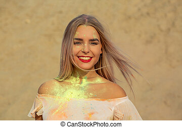 Closeup portrait of smiling blonde girl with red lips playing with green dry paint Holi at the desert