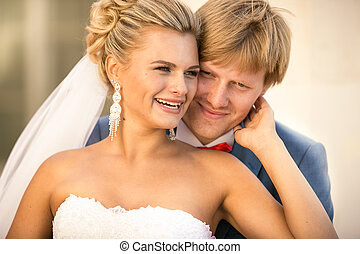 portrait of smiling bride and groom hugging on street at sunny d