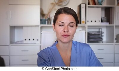 Closeup portrait of smiling female professional health worker in medical office. High quality FullHD footage