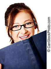 Closeup portrait of smiling girl with a book.