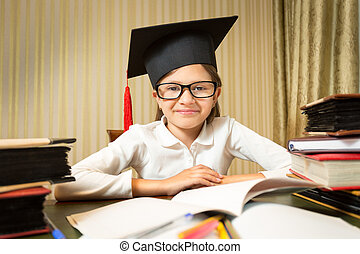 portrait of smiling little girl in graduation hat sitting at...