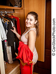 portrait of smiling woman picking clothes at wardrobe