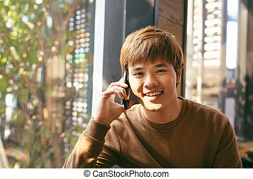 Closeup portrait of smiling young Asian man talking on mobile phone and sitting at empty table with blurred cafe interior in background