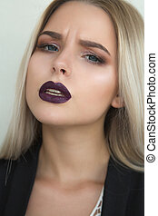 Closeup portrait of stunning blonde woman with purple lips and straight hair