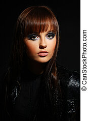 stylish young woman with evening makeup on a black background