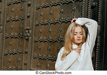 Closeup portrait of tender model with natural makeup posing near metal wrought door. Space for text