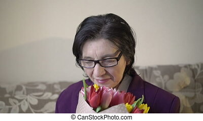 Closeup portrait of woman in her 70s holding the bouquet of flowers and smiling