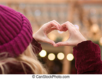 Closeup portrait of woman making heart shape from her fingers on a background of city lights