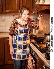 portrait of woman trying soup with ladle - Closeup portrait...