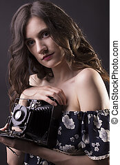 Closeup portrait of woman with vintage camera