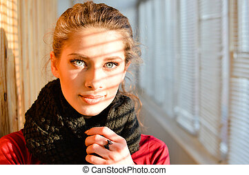 closeup portrait of wonderful beautiful young woman with blue eyes in shawl on a balcony window background looking at camera
