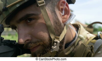 Closeup portrait of young army ranger aiming gun during a...
