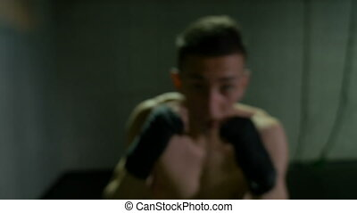 Closeup portrait of young athlete throwing punches and boxing in the training club