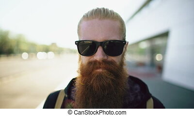 Closeup portrait of young bearded hipster man in sunglasses...