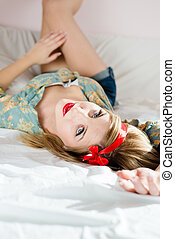 closeup portrait of young beautiful blond woman jeans shorts floral shirt lying on back white bed putting your feet on wall & looking at camera