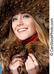 Closeup portrait of young beautiful girl wearing fur cap