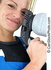closeup portrait of young blonde female apprentice holding spot welder