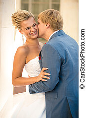 portrait of young groom kissing bride on street at sunny day