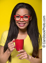 Closeup portrait of young happy woman. student wearing red glasses, holding cup