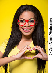Closeup portrait of young happy woman. student wearing red glasses, showing heart sign