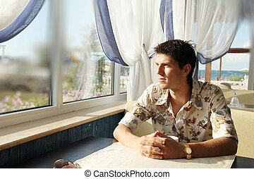 Closeup portrait of  young man looking at window