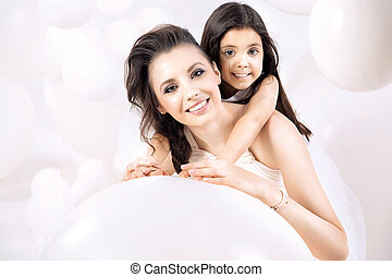 Closeup portrait of young mom with a cute daughter