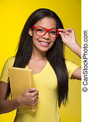 Closeup portrait of young smiling woman. student wearing red glasses, holding book