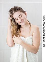 Closeup portrait of young smiling woman wiping wet hair after having shower