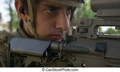 Closeup portrait of young soldier defending point in rural...