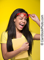 Closeup portrait of young winking woman. student wearing red glasses, holding book