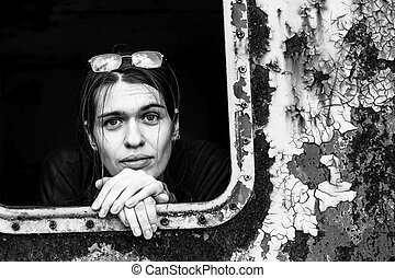 Closeup portrait of young woman looking out the window of an old industrial facility. Contrast black and white photography.