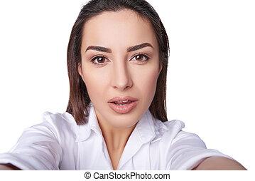 Closeup portrait of young woman taking selfie