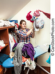 young woman trying to cope with flying clothes with iron