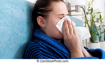 Closeup portrait of young woman with allergy sneezing in paper tissue