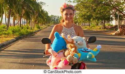Closeup Pretty Girl Rides Motorbike along Street with Palms