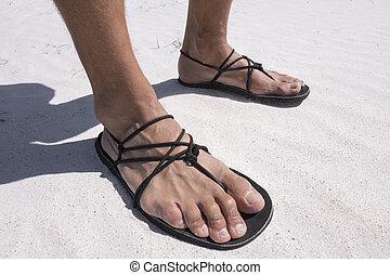 Closeup primitive sandals worn on beach