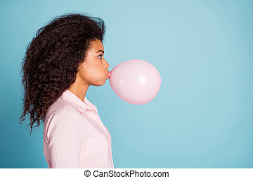 Closeup profile photo of pretty dark skin lady holding big air balloon in mouth making decorations for surprise party wear pink shirt isolated blue color background