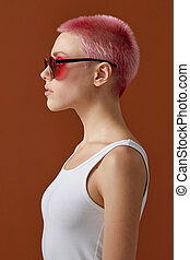 Closeup profile portrait of a girl with pink short hair in sunglasses, over brown background.
