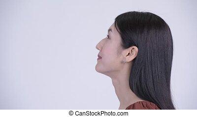 Closeup profile view of happy beautiful Asian woman looking...