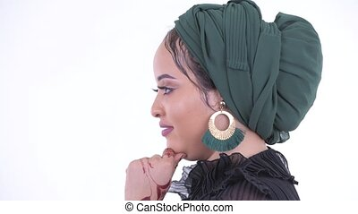 Closeup profile view of happy young African Muslim woman...