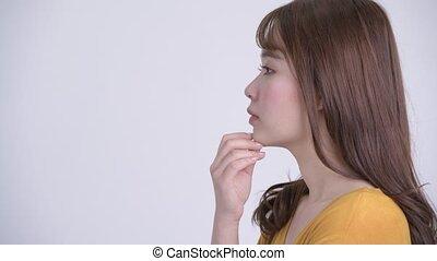 Closeup profile view of happy young beautiful Asian woman thinking
