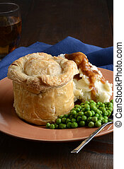 closeup pub meat pie with vegetables and gravy