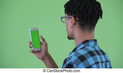 Closeup rear view of happy young African hipster man using phone