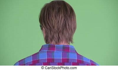 Closeup rear view of young hipster man looking around