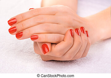 Closeup red manicure on the white towel