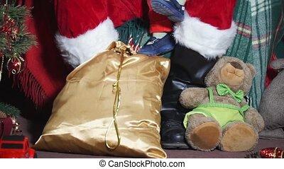 Closeup Santa shows baby toy on the Christmas tree