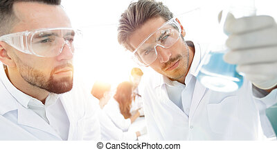 closeup. scientist and assistant studying the solution in...