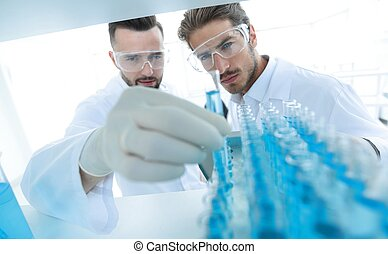 scientist and assistant studying the solution in the tube