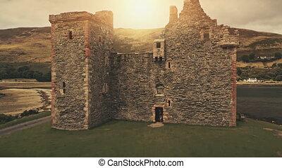 Closeup castle ruin aerial. Sun over mountains. Tourist attraction of Hamilton dynasty palace. Nature seascape of Loch-Ranza Bay, Arran island, Scotland, United Kingdom, Europe. Rise up drone shot